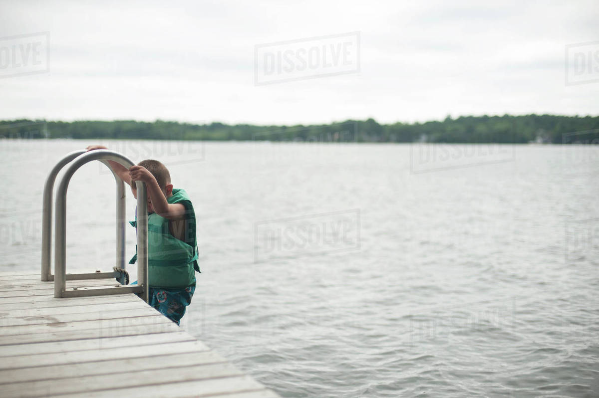 Boy climbing ladder of jetty against sky Royalty-free stock photo