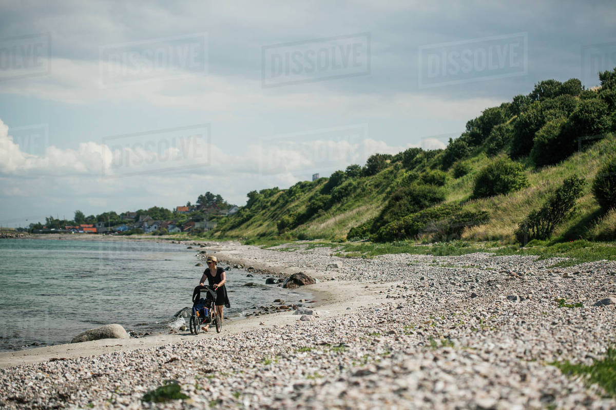Denmark, Zealand, Nyby, Woman with baby carriage walking along coastline Royalty-free stock photo
