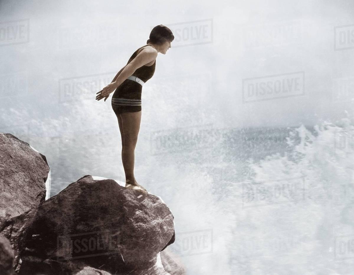 Female swimmer on rock above crashing surf Royalty-free stock photo
