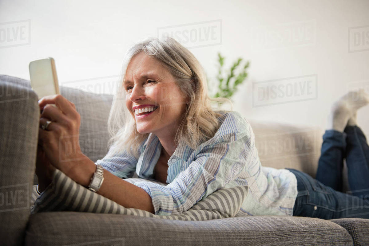 Smiling woman laying on sofa texting on cell phone Royalty-free stock photo