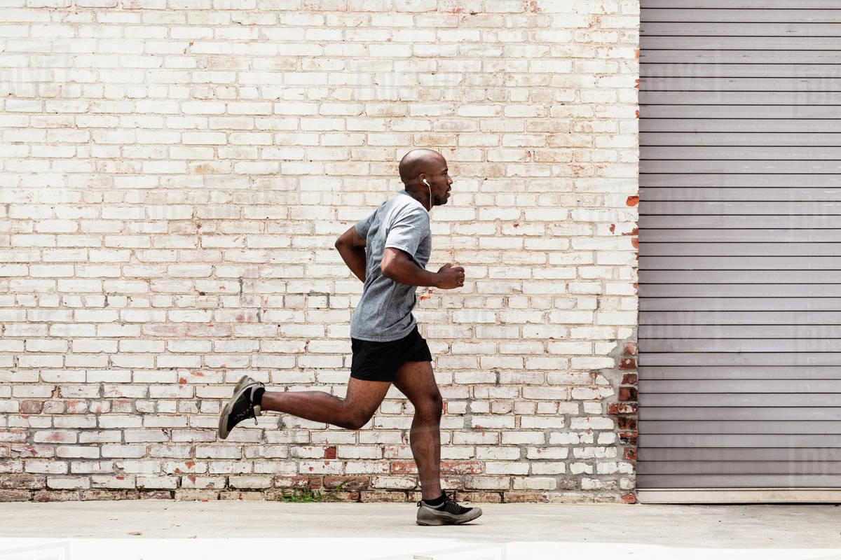 Black man running on city sidewalk Royalty-free stock photo