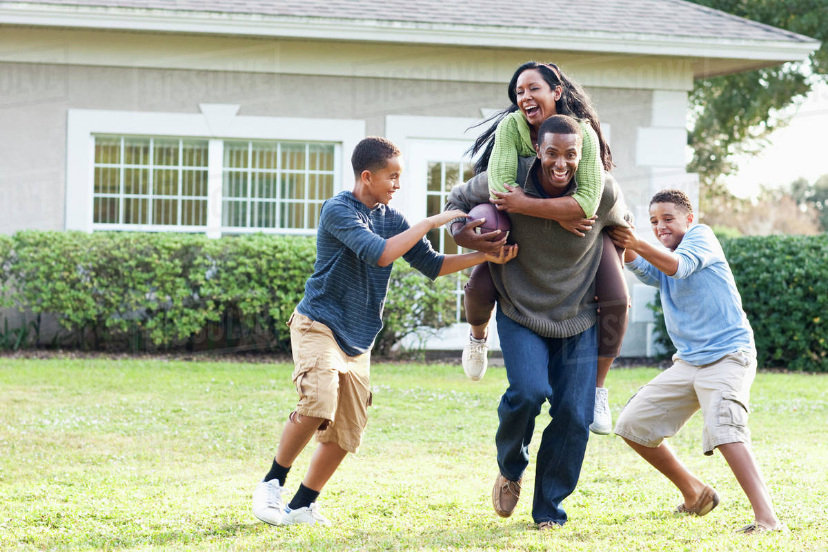 family playing football in backyard stock photo dissolve