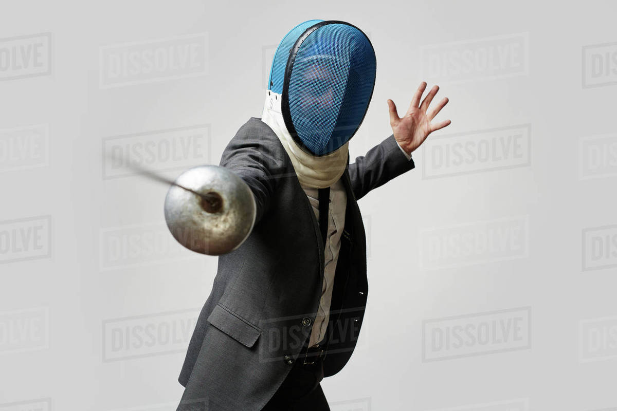 Businessman in fencing mask and formal suit attacking his rival with foil to defense himself and his business or company in economically hard period Royalty-free stock photo