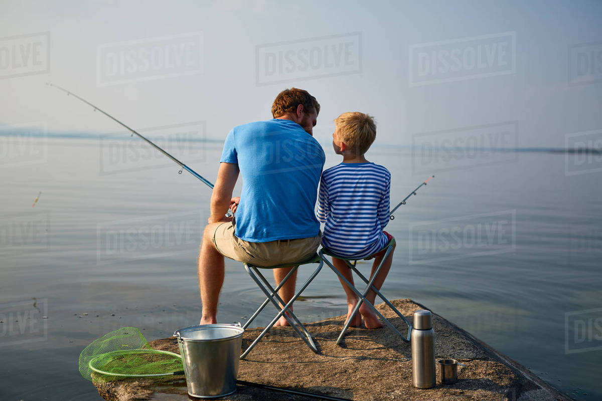 Boy and his father with rods sitting on chairs by lake Royalty-free stock photo