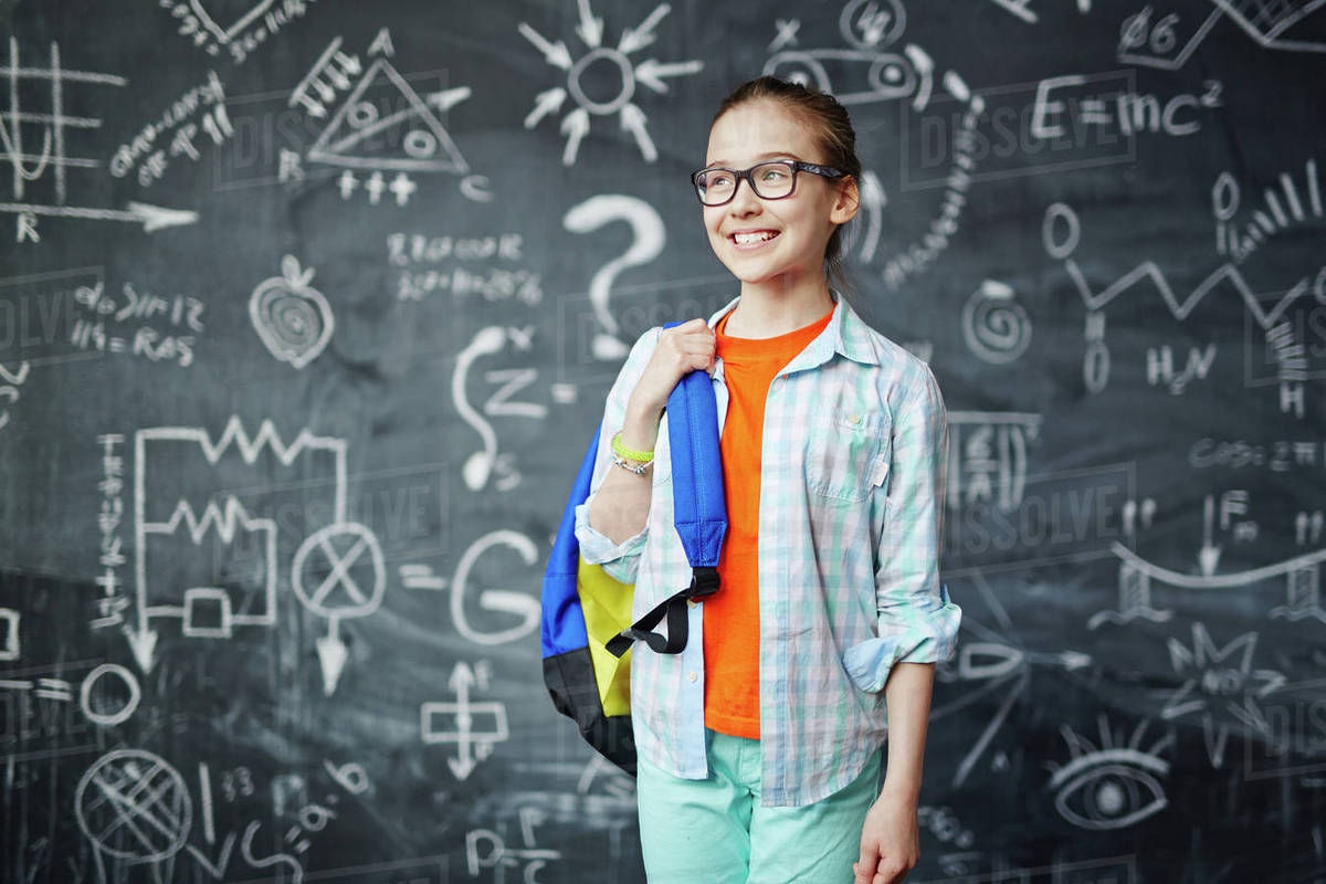 Clever schoolgirl with blue backpack on background of blackboard Royalty-free stock photo