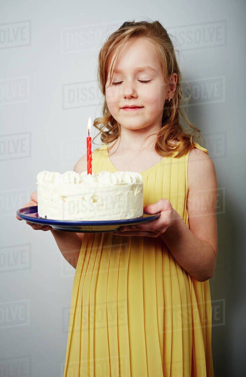 Cute girl holding birthday cake with burning candle and making wish Royalty-free stock photo