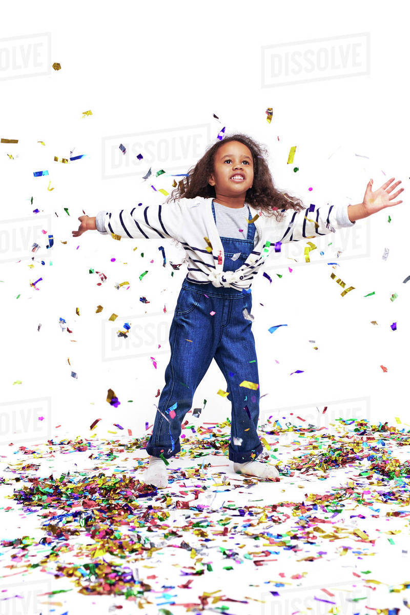 Funny girl in casual-wear playing with confetti Royalty-free stock photo
