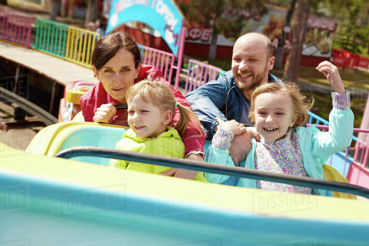 Family of four having fun in amusement park Royalty-free stock photo