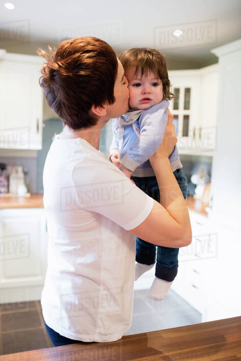 Cute mother kissing her baby in the kitchen Royalty-free stock photo