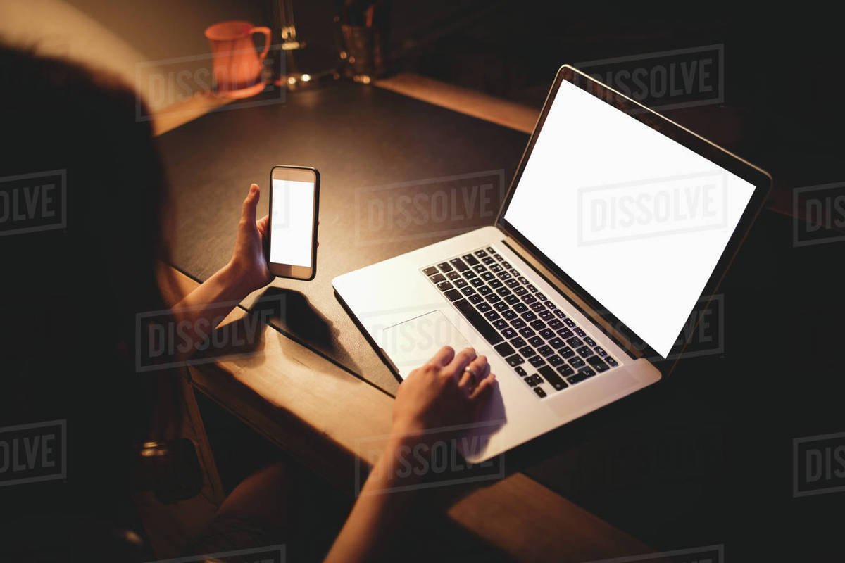 Brunette using laptop and smartphone on desk at home Royalty-free stock photo