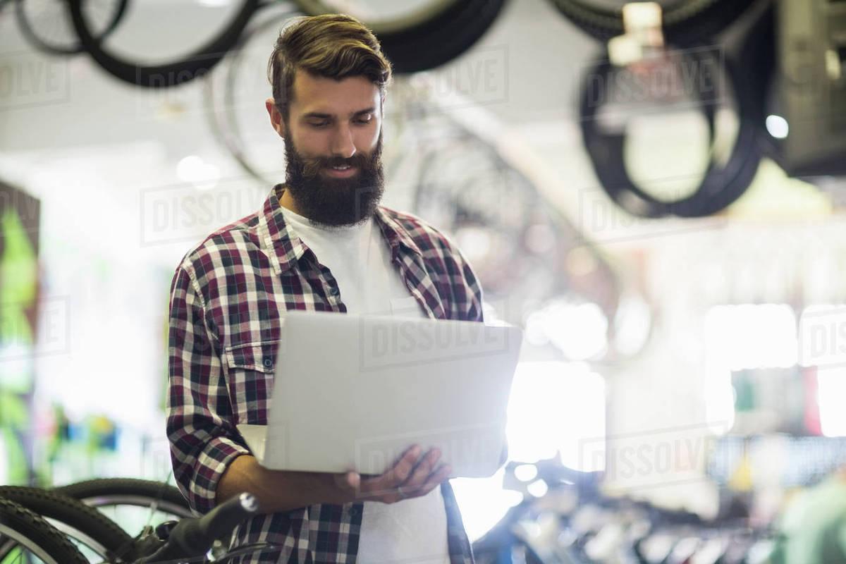 Bike mechanic checking laptop in bike repair shop Royalty-free stock photo