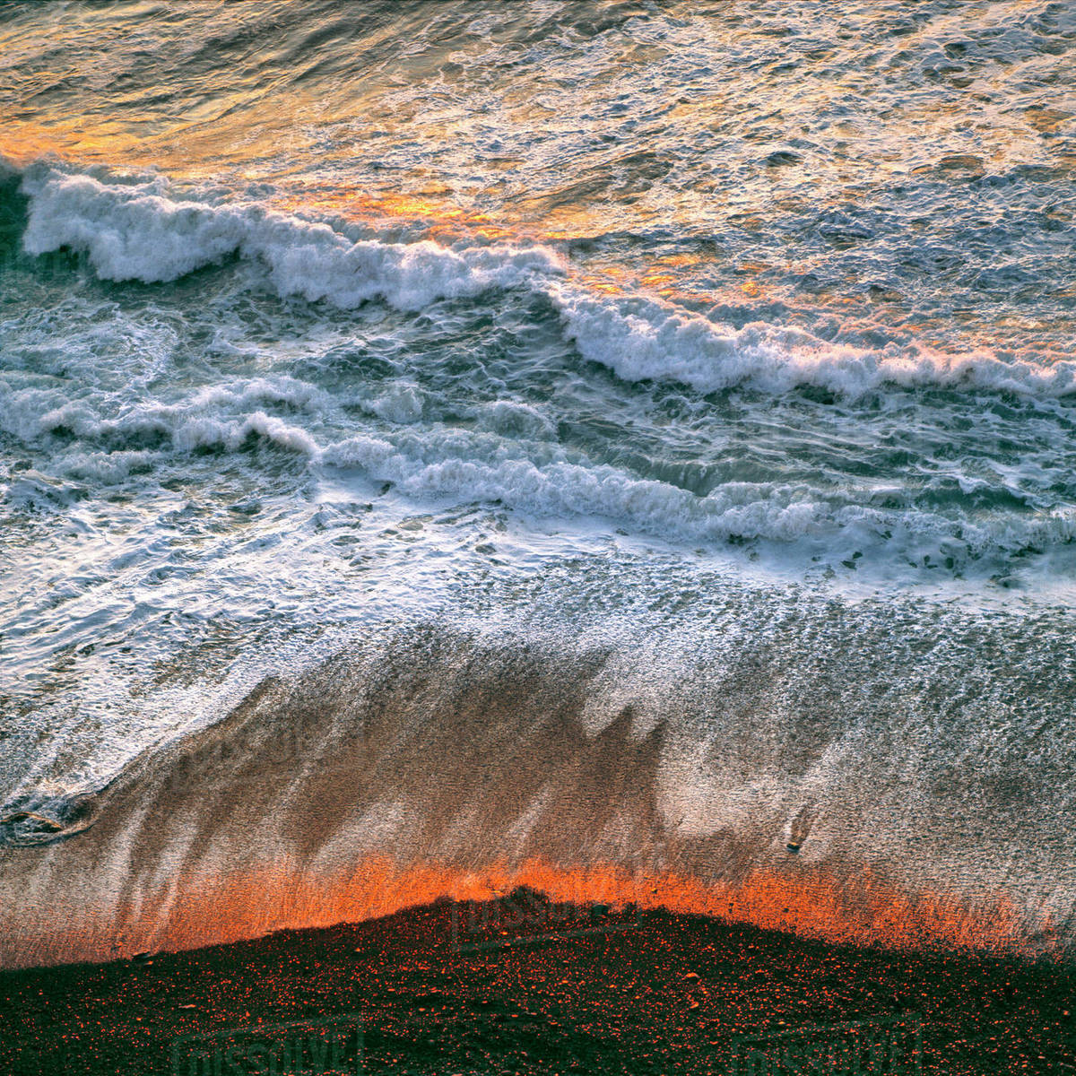 USA, California, Big Sur. Breaking surf catches the late fiery light of sunset at Big Sur on the California coast. Royalty-free stock photo