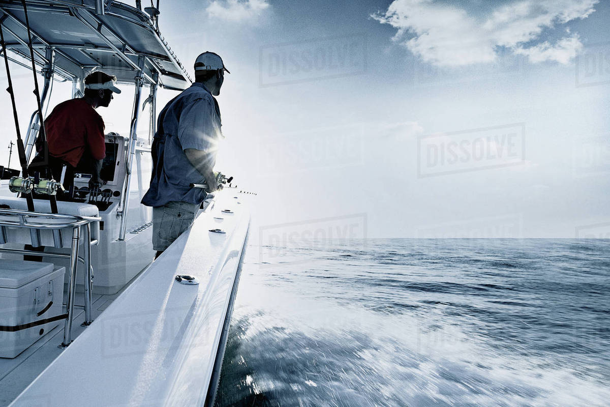 Monochromatic shot of two men driving and fishing from speedboat, Miami, USA Royalty-free stock photo