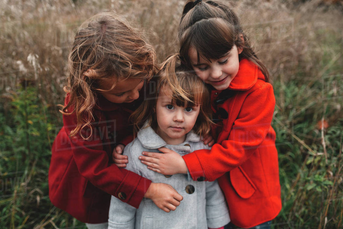 Portrait of two girls hugging toddler sister in field Royalty-free stock photo