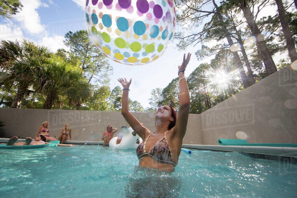 Woman playing throwing beach ball in swimming pool, Santa Rosa Beach, Florida, USA Royalty-free stock photo