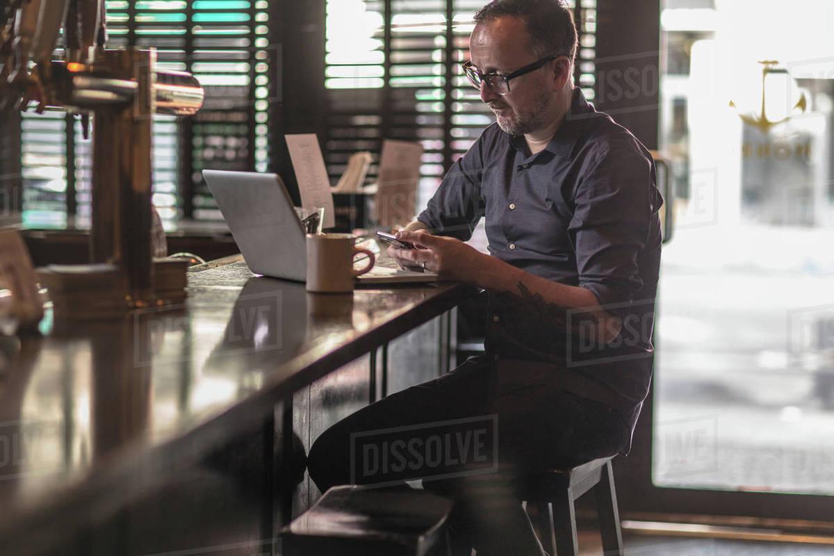 Barman reading smartphone texts at public house counter Royalty-free stock photo