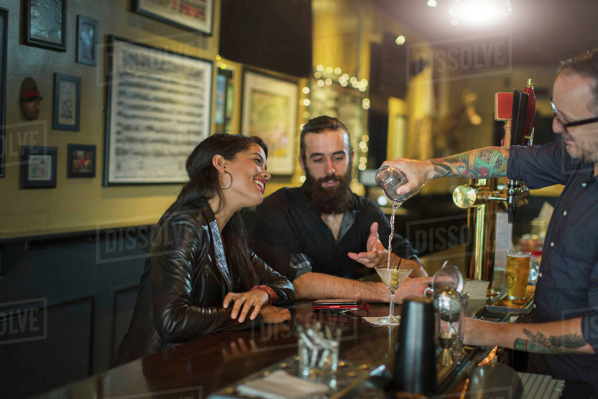 Bartender pouring cocktail for young couple in public house Royalty-free stock photo