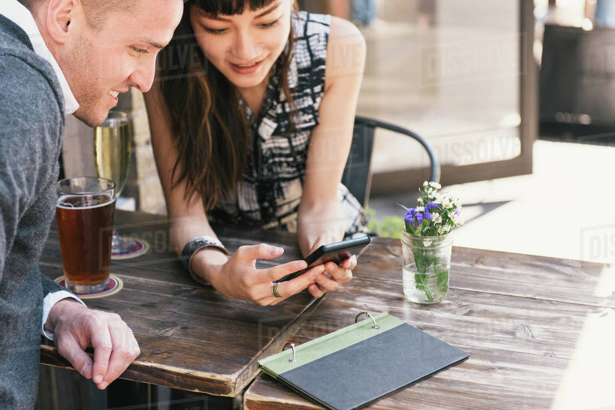Young couple sitting outside bar, looking at smartphone Royalty-free stock photo