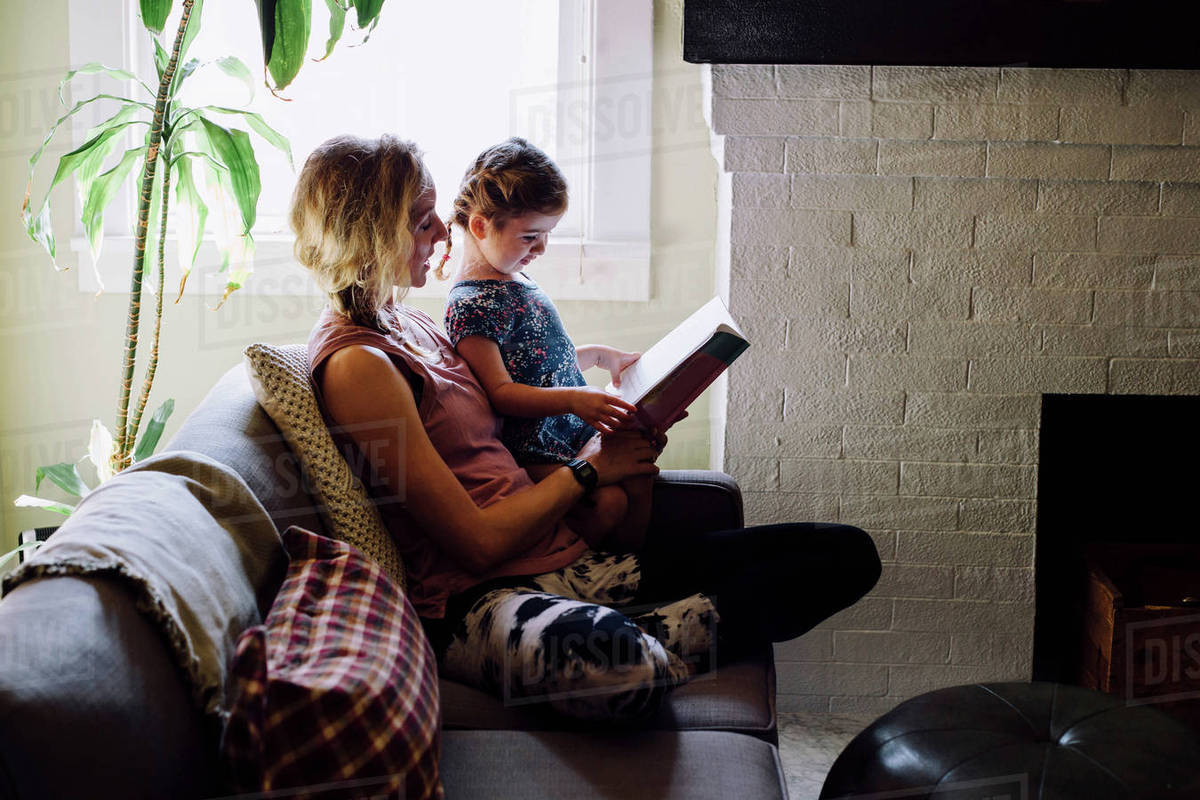 Woman on sofa with toddler daughter reading storybook Royalty-free stock photo
