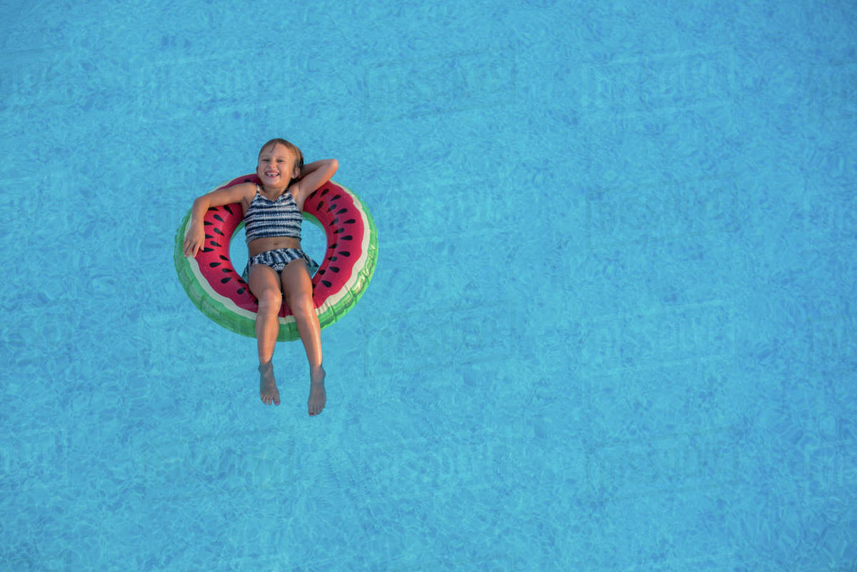 Young girl in swimming pool, relaxing on inflatable ring Royalty-free stock photo