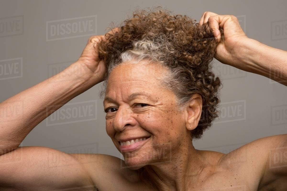 Close up studio portrait of senior woman pulling her hair Royalty-free stock photo