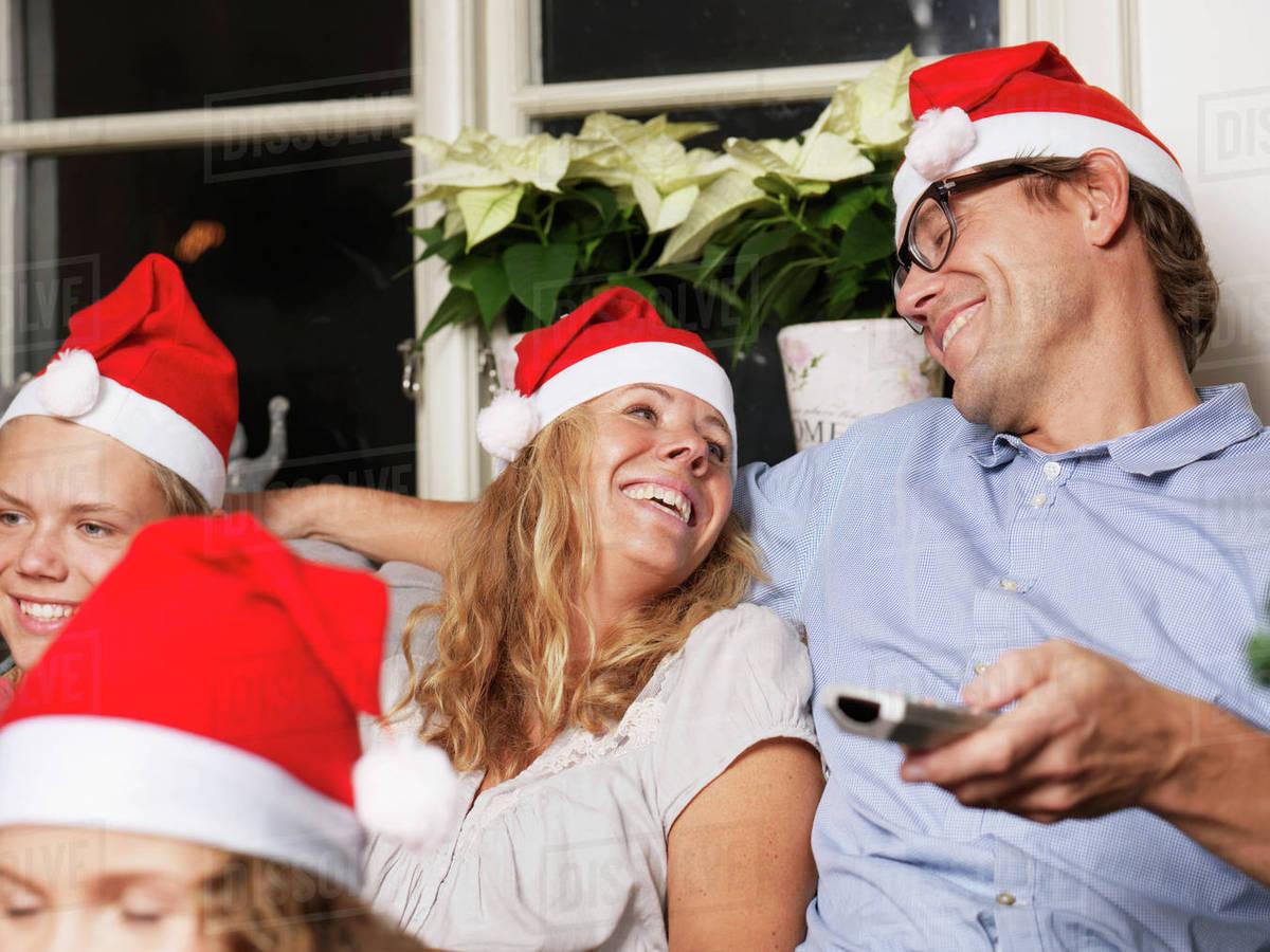 Family wearing Santa hats on sofa Royalty-free stock photo