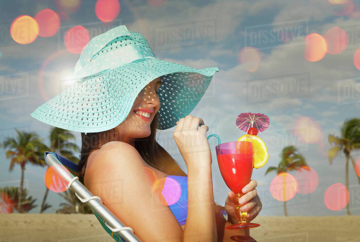 Young woman sitting on deckchair with cocktail at Miami beach, Florida, USA Royalty-free stock photo