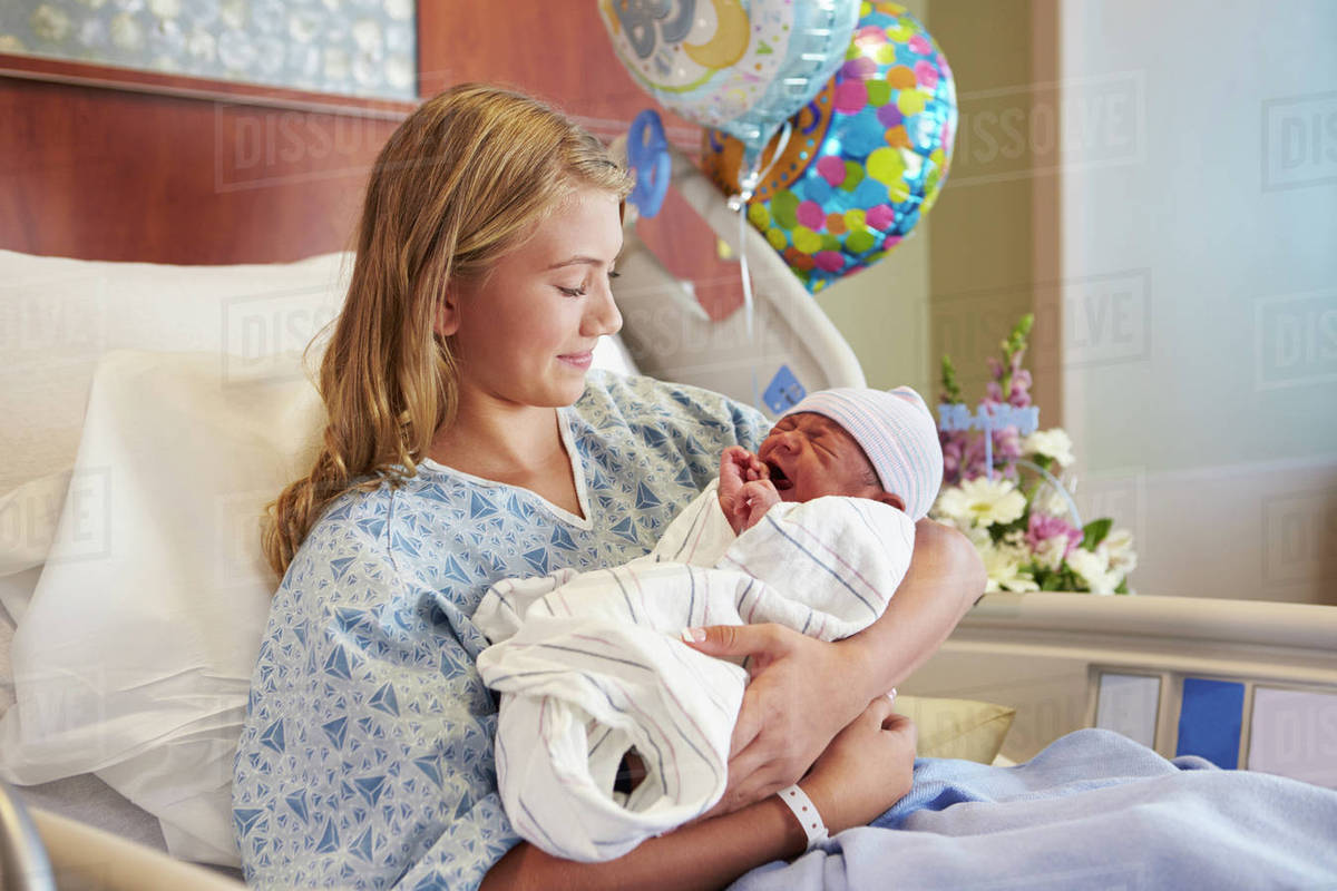 teenage girl holding newborn baby son in hospital stock