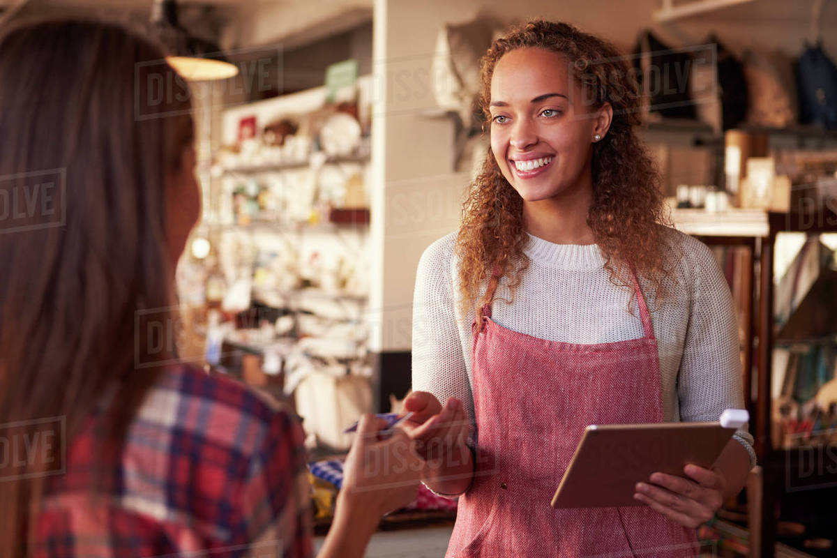 Sales assistant with credit card reader on digital tablet Royalty-free stock photo