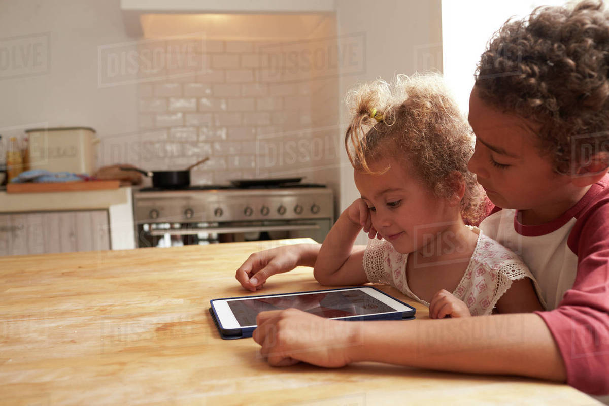 Children At Home Using Digital Tablet On Kitchen Table Royalty-free stock photo