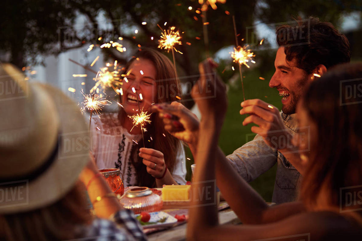 Friends With Sparklers Eating Food And Enjoying Party Royalty-free stock photo