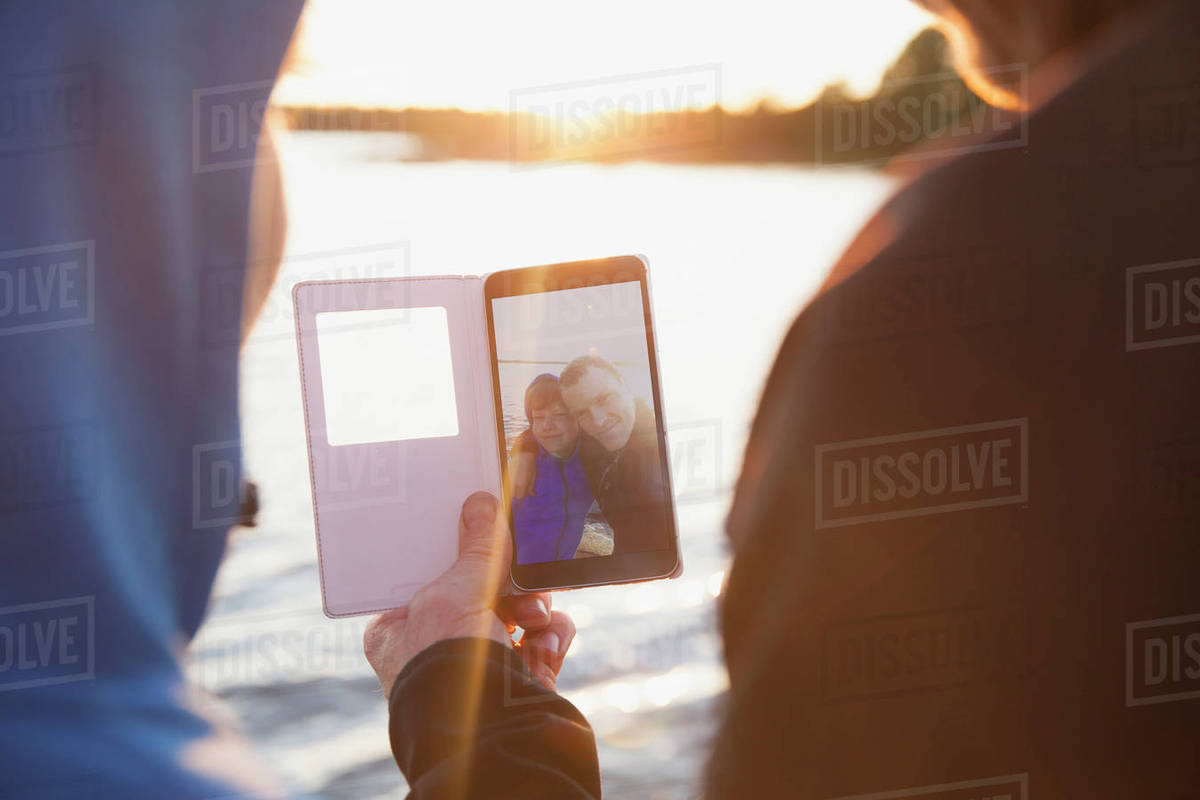 Rear view of man and boy looking at photograph in smart phone against lake Royalty-free stock photo
