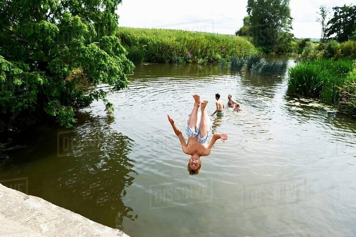 Teenage boy somersaulting into rural lake Royalty-free stock photo