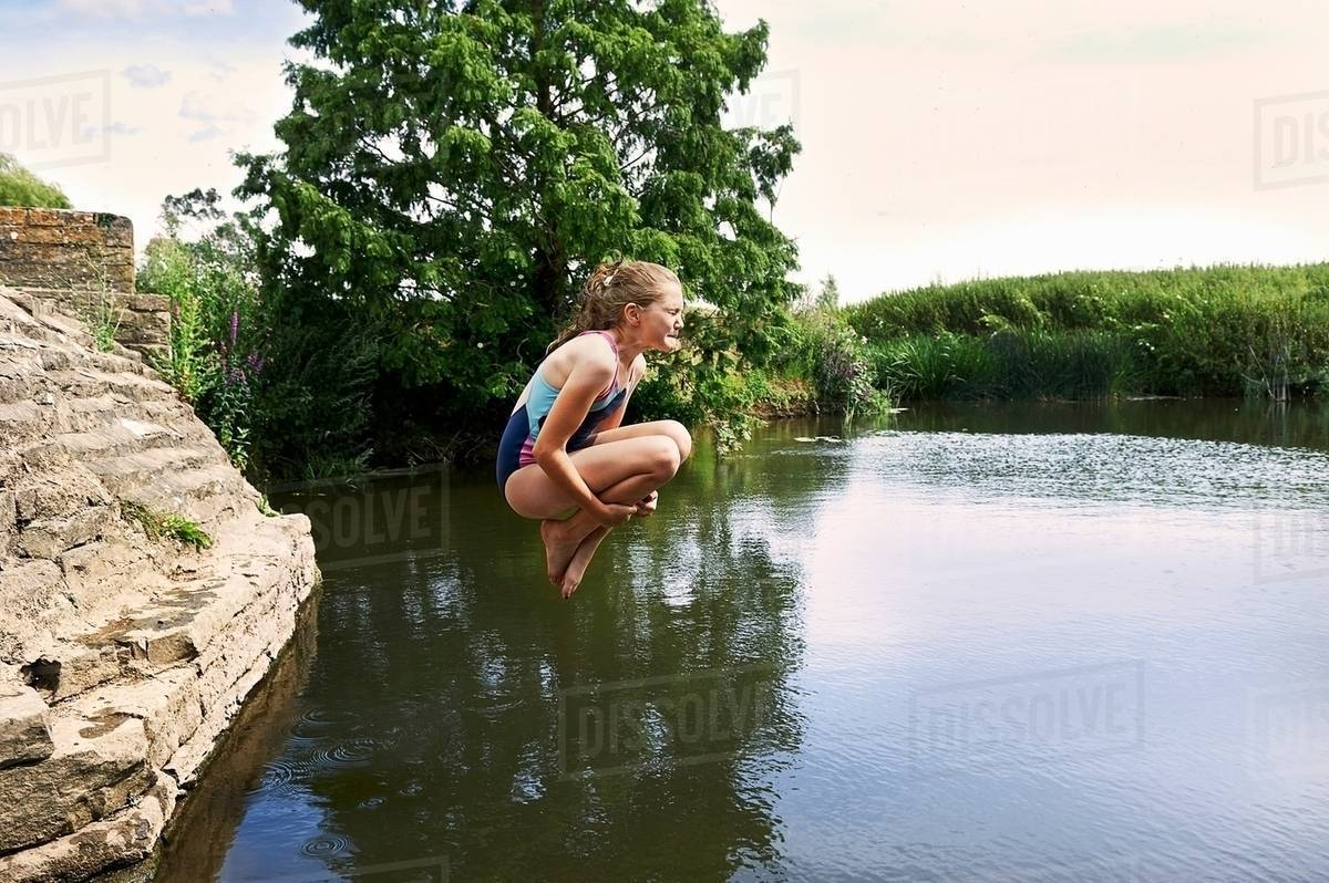 Side view of girl jumping into lake Royalty-free stock photo
