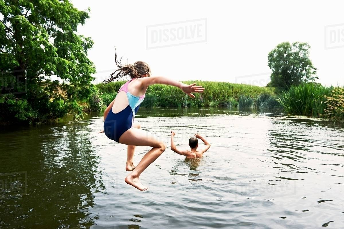Teenage boy and sister jumping into lake Royalty-free stock photo