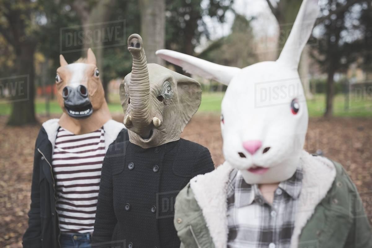 Three sisters wearing animal masks posing in park Royalty-free stock photo