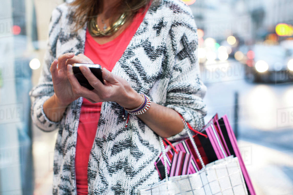 Woman using smartphone while shopping Royalty-free stock photo