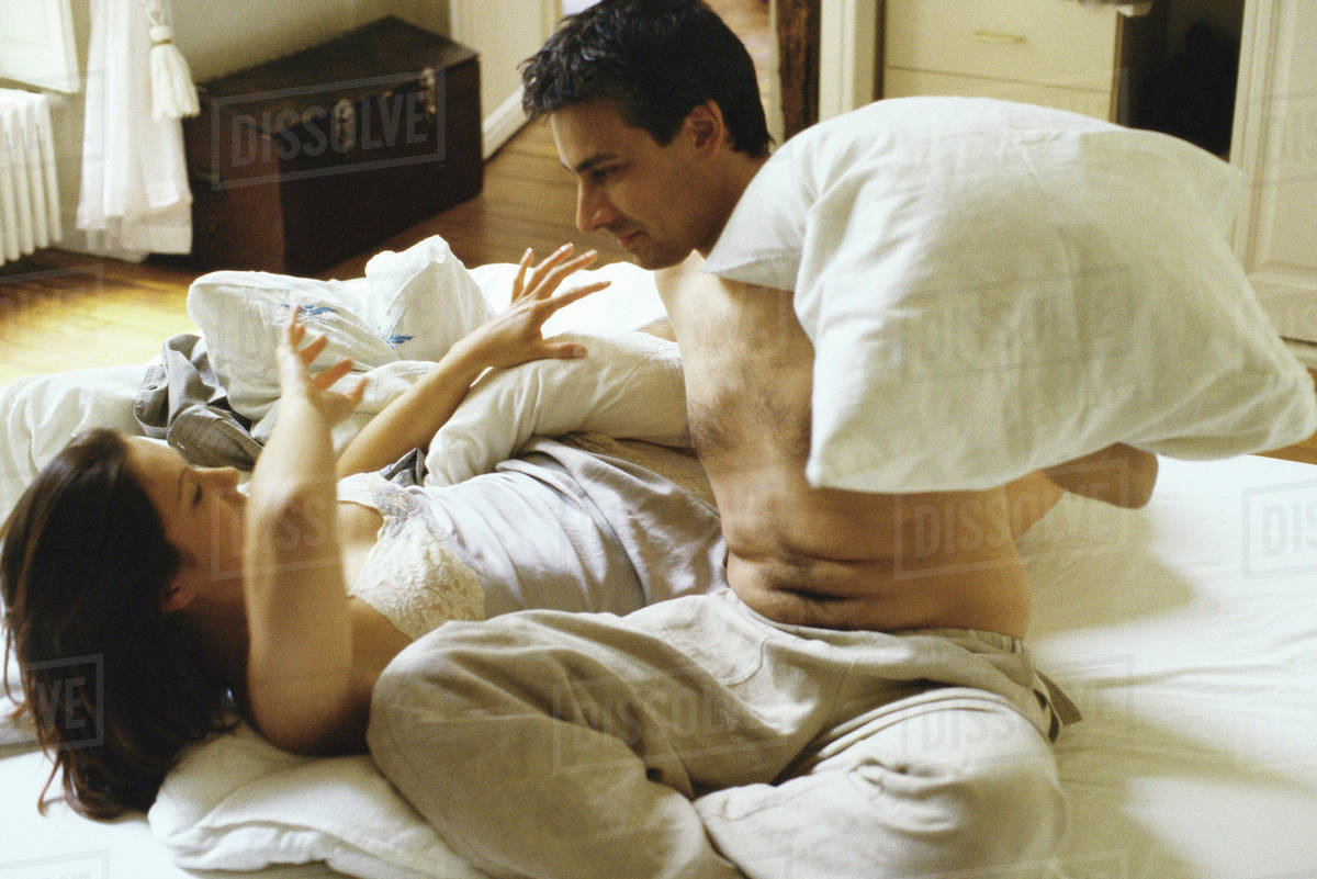 Couple Having Pillow Fight In Bed Stock Photo Dissolve