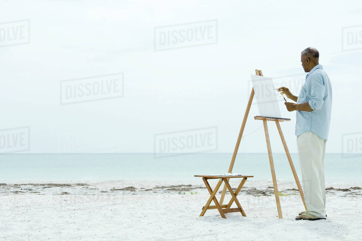 Beach lounge chair side view - Senior Man Painting On Canvas At The Beach Side View