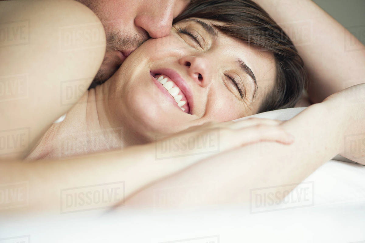 Couple Cuddling In Bed Husband Kissing Wife