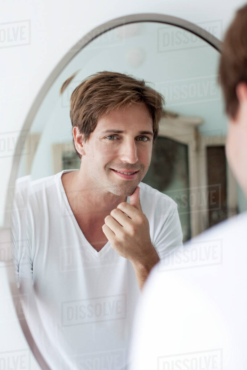 man looking in mirror. man looking at self in mirror touching facial stubble i