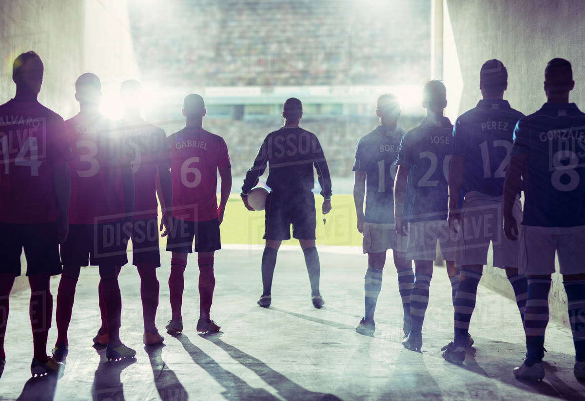 silhouette of soccer teams facing field