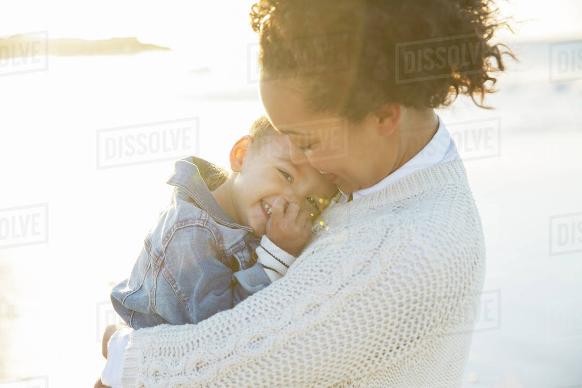 Young woman embracing daughter on beach Royalty-free stock photo