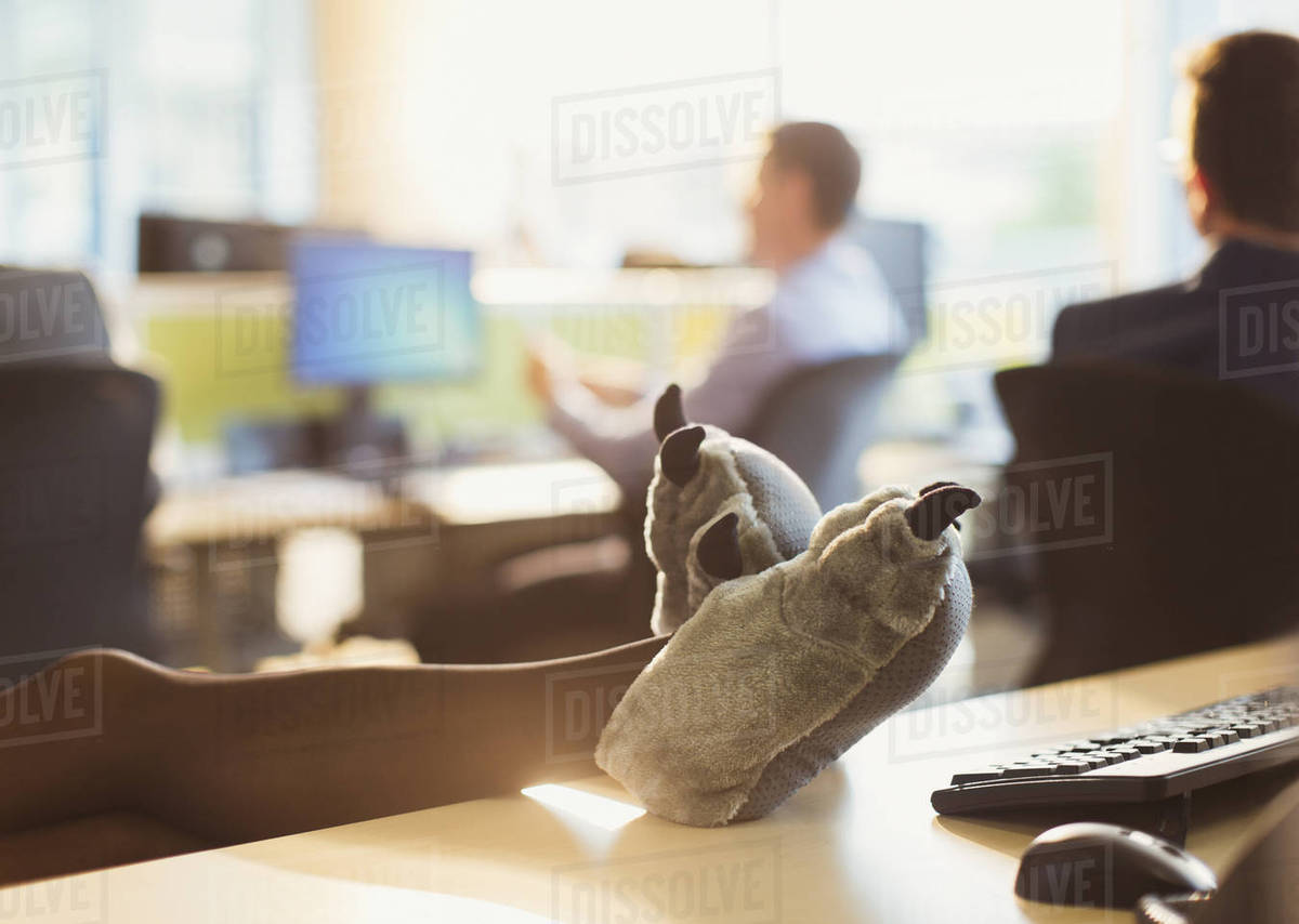 Businesswoman wearing wolf paw slippers with feet up on office desk Royalty-free stock photo