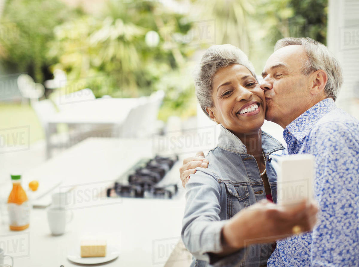 Affectionate mature couple kissing taking selfie in kitchen Royalty-free stock photo