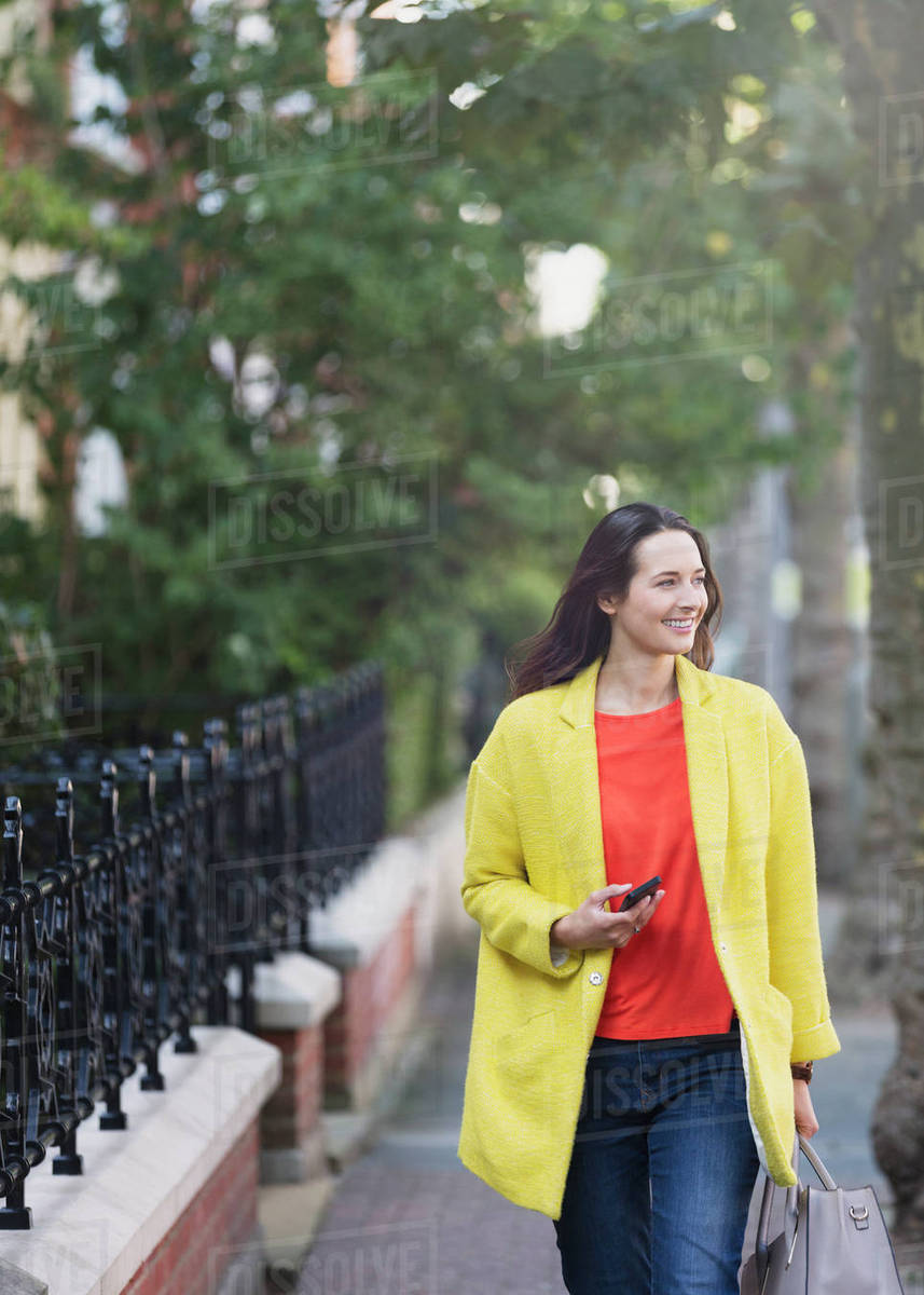 Smiling woman walking with cell phone in urban park Royalty-free stock photo