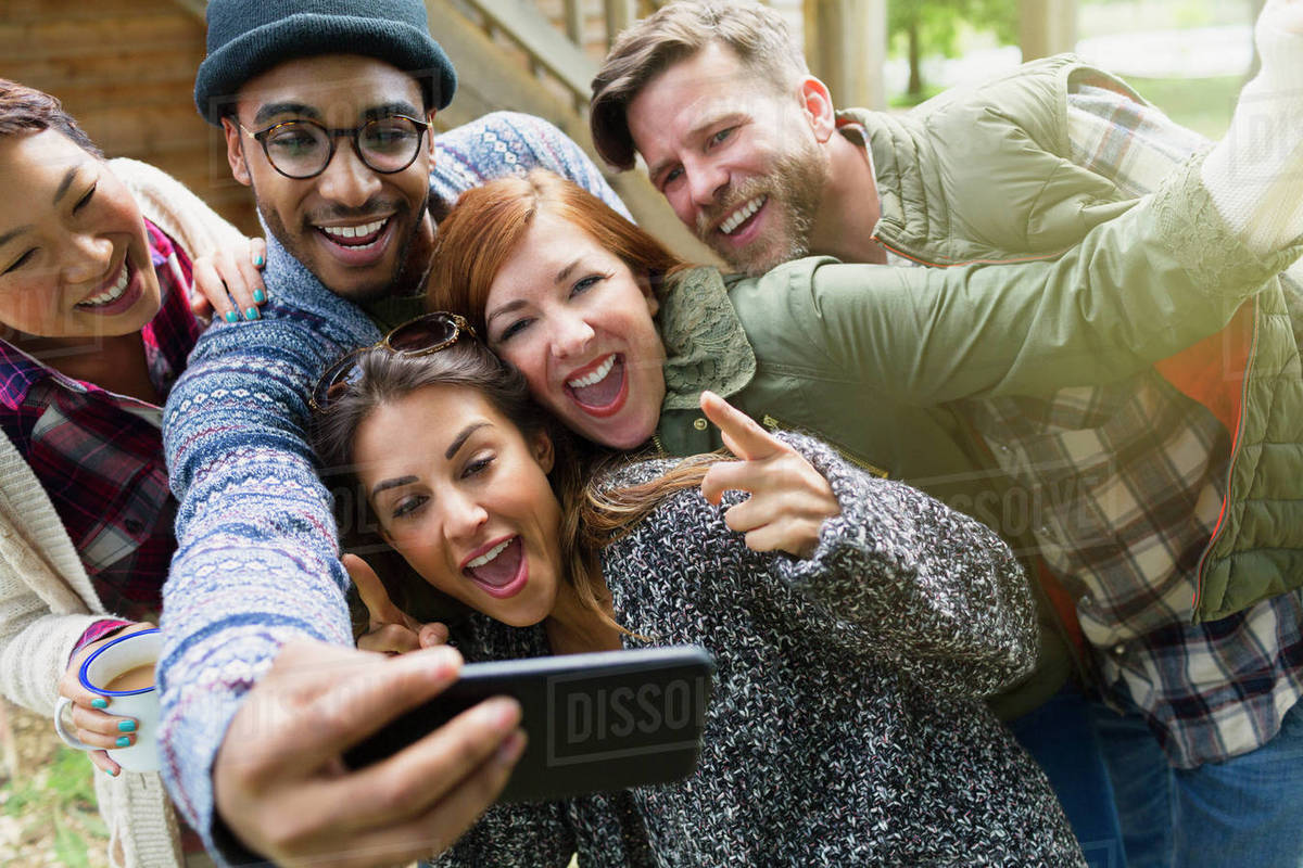 Playful friends with camera phone gesturing taking selfie Royalty-free stock photo