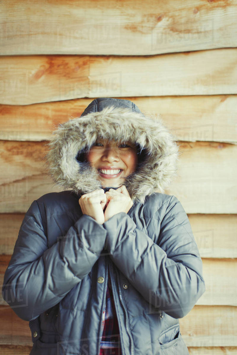 Portrait smiling woman wearing fur hood coat outside cabin Royalty-free stock photo