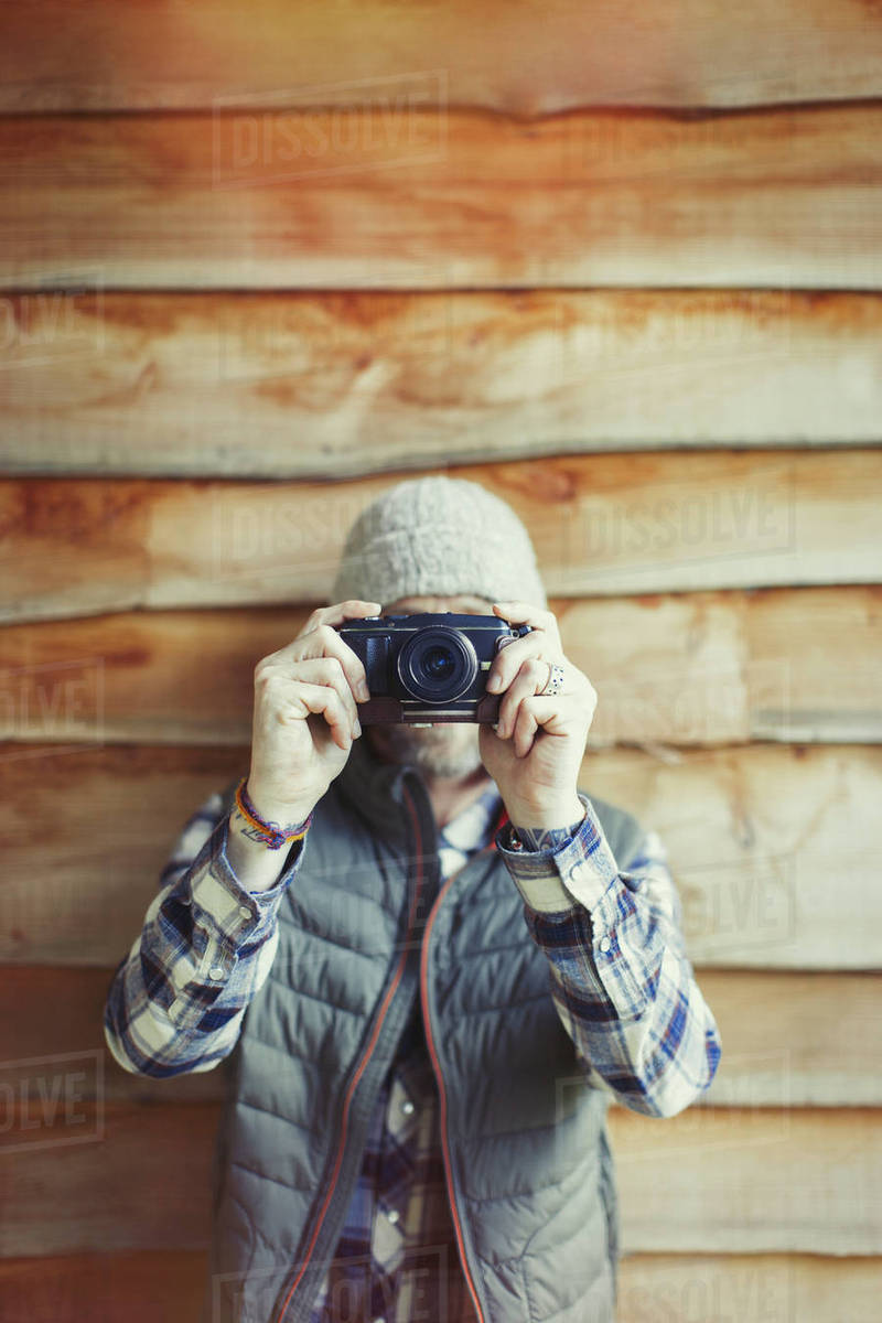 Portrait man using camera outside cabin Royalty-free stock photo