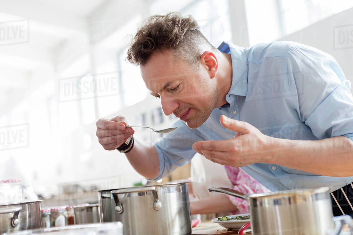 Man Smelling Food Leaning Over Pot In Cooking Class Kitchen